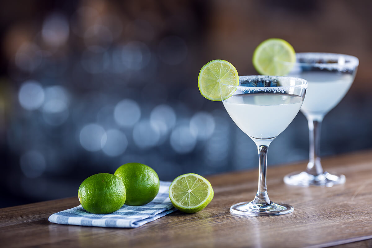 Image of a Barrel Aged Margarita with limes on a bar