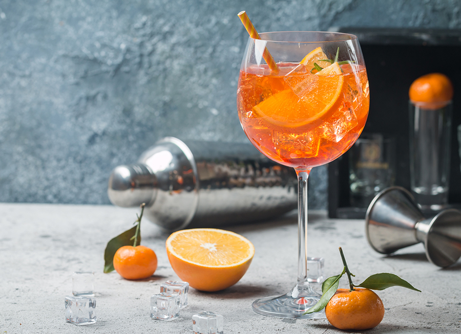Image of Aperol Spritz with orange slices, cocktail shaker and jigger