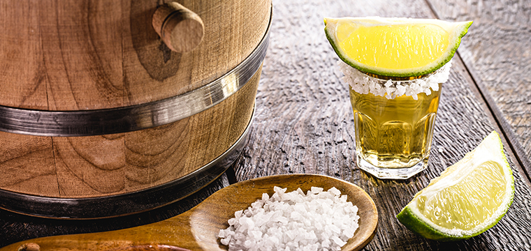 Photo of a shot of tequila and an oak barrel