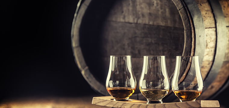Photo of three glasses of whiskey and an oak barrel