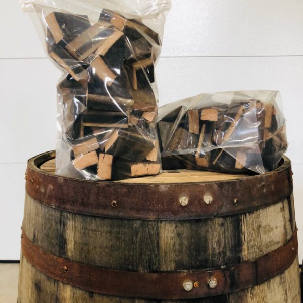 Photo of two bags of whiskey barrel chunks on an oak barrel